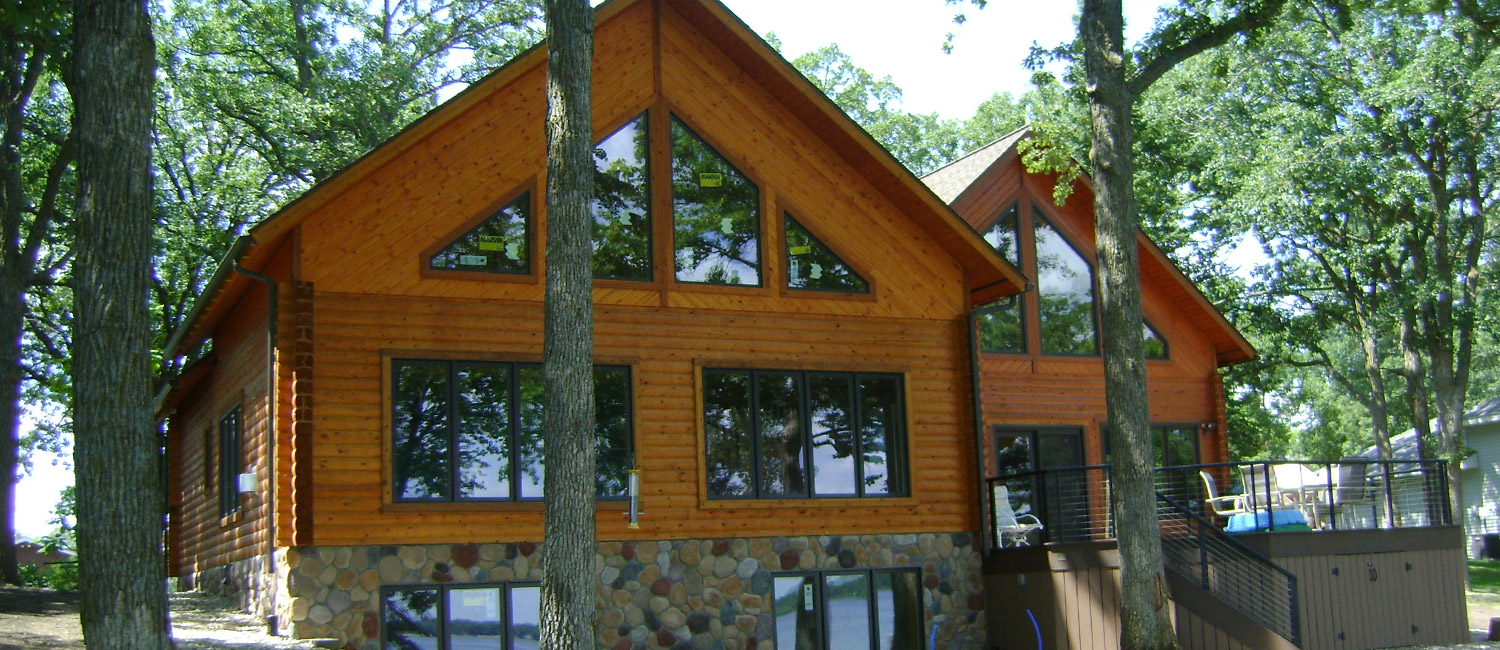 Exterior of am A-Frame style log home with large windows